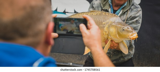 Unknown man photographing a big fish caught in the lake as a souvenir.
