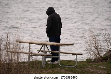 unknown man stands alone at the lake and watches the water