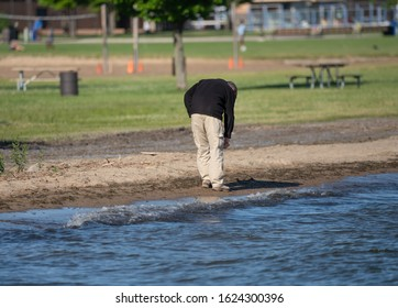 unknown man stops to pick up a treasure while at the beach