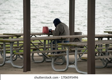 unknown man takes a break to have his lunch at the park