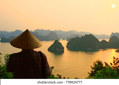 Unknown man watching the beautiful landscape of Ha Long Bay with islands and cliffs at sunset, Vietnam