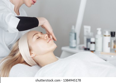 Unknown masseuse beautician doing a face massage to her client a beautiful young woman. Skin care concept