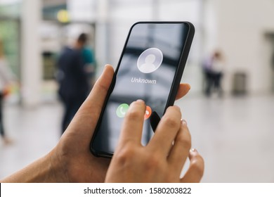Unknown number calling in the ctiy. Phone call from stranger. Person holding mobile and smartphone at a trade fair. Unexpected call disturbs at business conference.