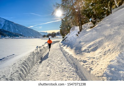 Unknown running man on the pass round the  lake Davos in winter resort Davos, Switzerland.