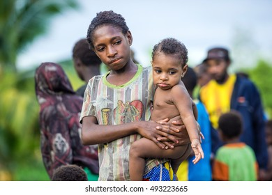 UNKNOWN SMALL VILLAGE, IRIAN JAYA, NEW GUINEA, INDONESIA - MAY 22, 2016: Portrait of unidentified Papuan little girl  holding baby boy on the hands. Asmat people village. New Guinea.May 22, 2016