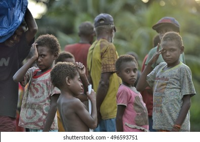 UNKNOWN SMALL VILLAGE, IRIAN JAYA, NEW GUINEA, INDONESIA - MAY 22, 2016: Portrait of Group of little papuan children  outdoors in evening twilight. Asmat people. New Guinea.May 22, 2016