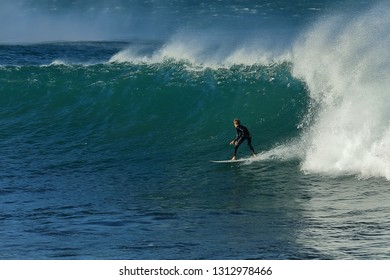 An unknown surfer enjoys himself at high tide on huge waves at Die Punt near Mossel Bay in South Africa.