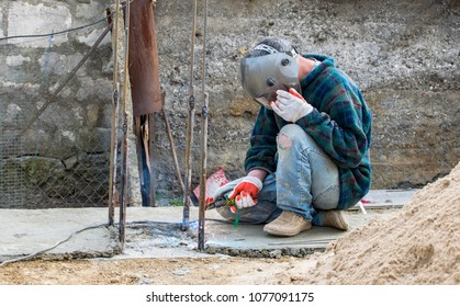 An unknown welding worker on the construction of a private house. Problems of labor migration. Illegal labor migration. Observance of safety in construction.