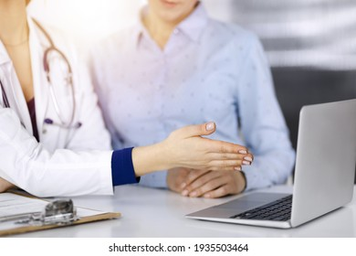 Unknown woman- doctor and her patient are discussing patient's blood test, while sitting together at the desk in the sunny cabinet in a clinic. Female physician, with a stethoscope, is using a laptop
