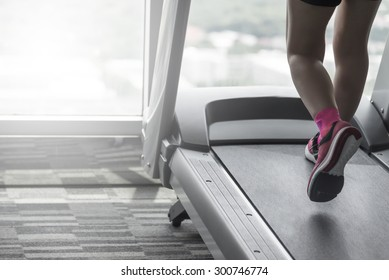 Unknown woman wear pink running shoes workout by thread mill in fitness