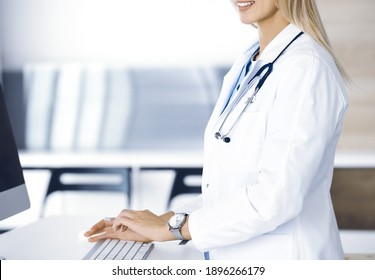 Unknown woman-doctor is typing on desktop computer at reception desk in clinic. Physician at work, close-up. Medicine concept