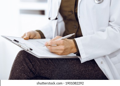 Unknown woman-doctor writing something at clipboard while sitting at the chair, close-up. Therapist wearing green blouse at work is filling up medication history record. Medicine concept