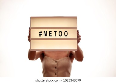 Unknown young woman covering her chest & face w/ #Metoo hashtag word on glowing lightbox isolated on white. Me too light box. Anti sexism protest movement against inappropriate behavior towards women.