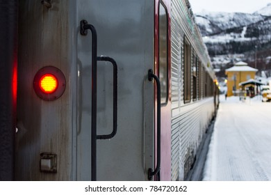 Unlabeled passenger coach of train in a snowy and cold train station next to the platform,  station and mountains in the background. Taken in Narvik, Norway and Train heads for Kiruna, Sweden