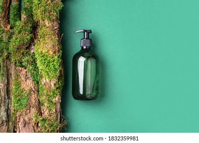 Unlabelled cosmetic bottle on green background, natural moss over branches, bark. Skin care, organic body treatment, spa concept. Vegan eco friendly cosmetology product. Organic cosmetics