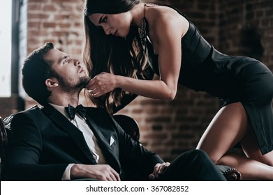 Unleashed desire. Beautiful young woman in cocktail dress leaning to her boyfriend sitting in chair while looking at each other in loft interior
