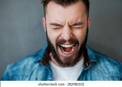 Unleashed emotions. Frustrated young man keeping eyes closed and mouth opened while standing against grey background