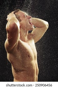 Unleashed freedom. Side view portrait of young sexual gay man taking a shower with water drops on his muscled body against black background