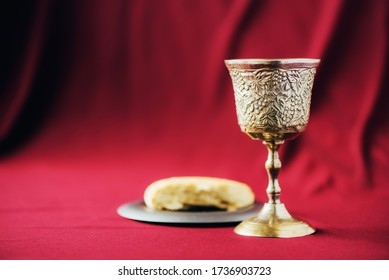 Unleavened bread, chalice of wine, silver kiddush wine cup on red background. Communion still life. Christian communion concept for reminder of Jesus sacrifice. Easter passover.