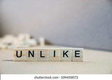unlike word written on wood block