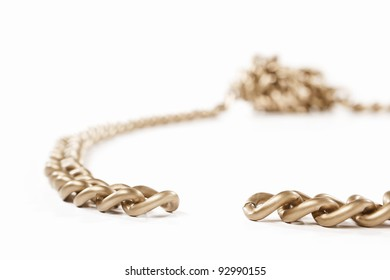 Unlinked part of the chain with twisted part o the other side, isolated against white background. small depth of field