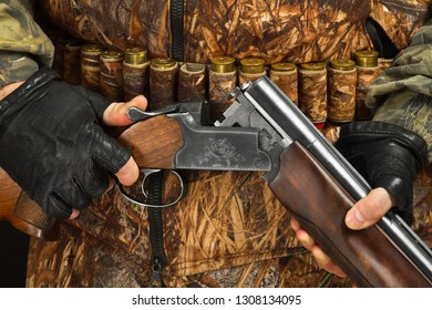 unloaded double-barreled shotgun in the hands of a hunter