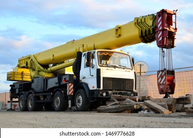 Unloading of cargo and building materials by mobile truck crane at the construction site. Auto crane during the construction of a bridge and highway. Roadwork concept, background texture - Image