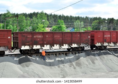 Unloading of crushed stone from railway car. Unloading bulk cargo from railway wagons on of high railway platform. Work with bulk cargo.
