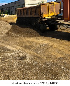 unloading of rubble.  large industrial truck unloads rubble from a trailer. lateral unloading of materials.