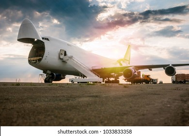 Unloading wide body transport cargo plane in the morning sun