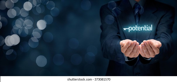 Unlock potential - motivational concept. Businessman with symbol of the key connected with text potential on hand. Wide banner composition with bokeh in background.