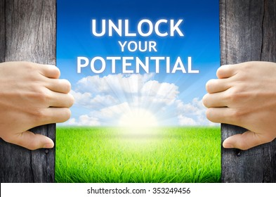 "Unlock your potential. Hand opening an old wooden door and found wording ""Unlock your potential"" over green field and bright blue Sky Sunrise."