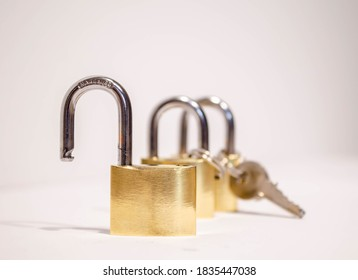 Unlocked golden padlock in front of two locked padlocks with keys on the white background close-up