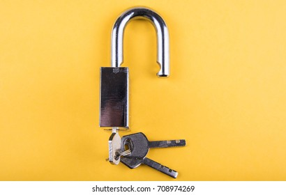 Unlocked Padlock And Key Isolated On Yellow Background