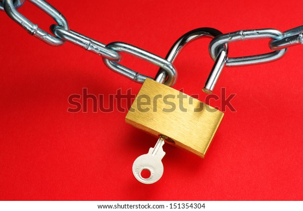 Unlocking padlock. Unlocking padlock and chain on red background.
