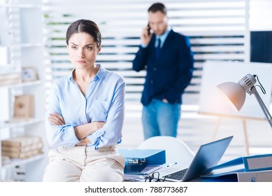 Unlucky day. Unhappy serious emotional woman sitting on the table with her arms crossed and frowning while thinking about the bad day at work with a young colleague standing behind her back