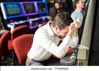 Unlucky young man feeling sad and stressed after losing his money playing slots in a casino