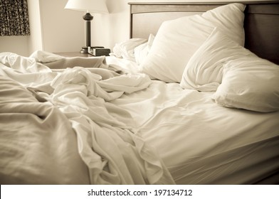 An unmade bed with pillows, sheets, and a blanket.