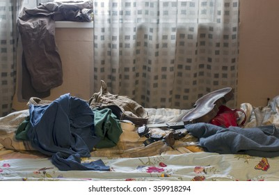 Unmade bed with ruffled blanket and various personal effects around in mess, indoor shot against the window
