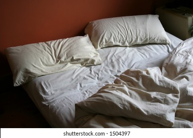Unmade Bed with white covers and red background