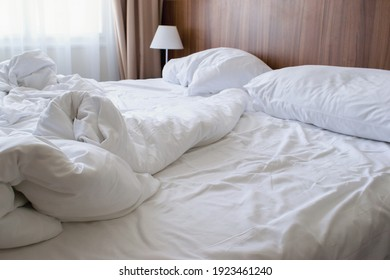 Unmade double bed with white linen in the morning