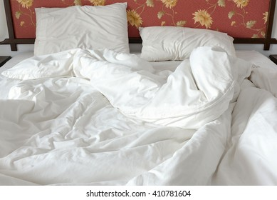 Unmade / untidy bed with a white crumpled blanket and two messy pillows in a bed room. Bedclothes are not neatly arranged for new customers / guests to sleep in. View from the foot of the bed.