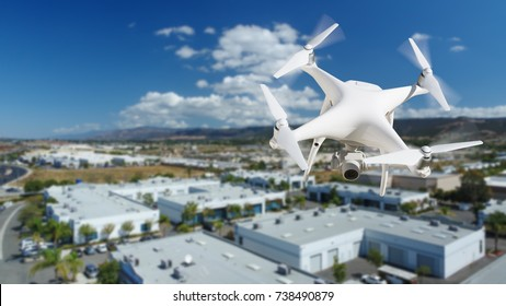 Unmanned Aircraft System (UAV) Quadcopter Drone In The Air Over Commercial Buildings.