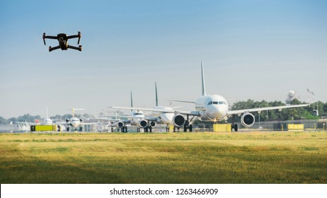 Unmanned drone flying near row of commercial airplanes at airport, flight disruption concept - digital composite