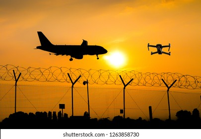 Unmanned drone flying over security fence at airport while commercial airplane prepares for landing, leading to possible collision - digital composite
