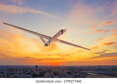 Unmanned military drone uav flying in the air over the city in evening sunset.