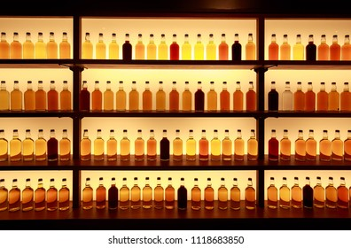 Unmarked glass whiskey bottles displayed on backlit shelves