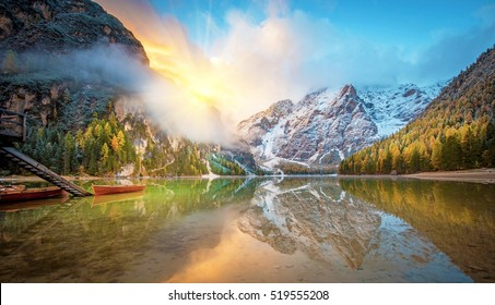 Unmatched autumn landscape with boat on the lake with sunrise on Fanes-Sennes-Braies natural park in the Dolomites in Alps, Italy, Europe. (mental vacation,  inner peace, harmony, honeymoon - concept)