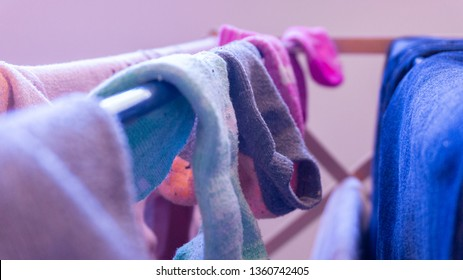 Unmatched socks drying on a rack, daytime. Depicting laundry day, cleaning, house chores and missing sock pairs.