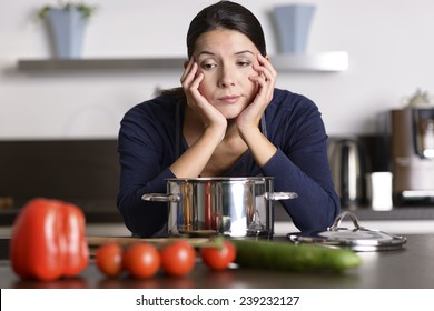 Unmotivated attractive young woman preparing the dinner leaning on the hob eyeing the fresh vegetables with a listless glum expression as she stands in her kitchen in an apron